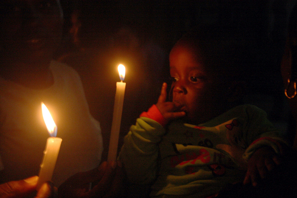 A picture taken on April 8, 2015 shows a child looking at two candles lit in commemoration of the 148 lives lost during a recent attack by the Al-Shabab insurgents in Garissa, Kenya. The Islamist terrorist group killed mostly students in the recent attacks in one of the biggest attacks in Kenya since 1998. PHOTO BY AMOS RIOT