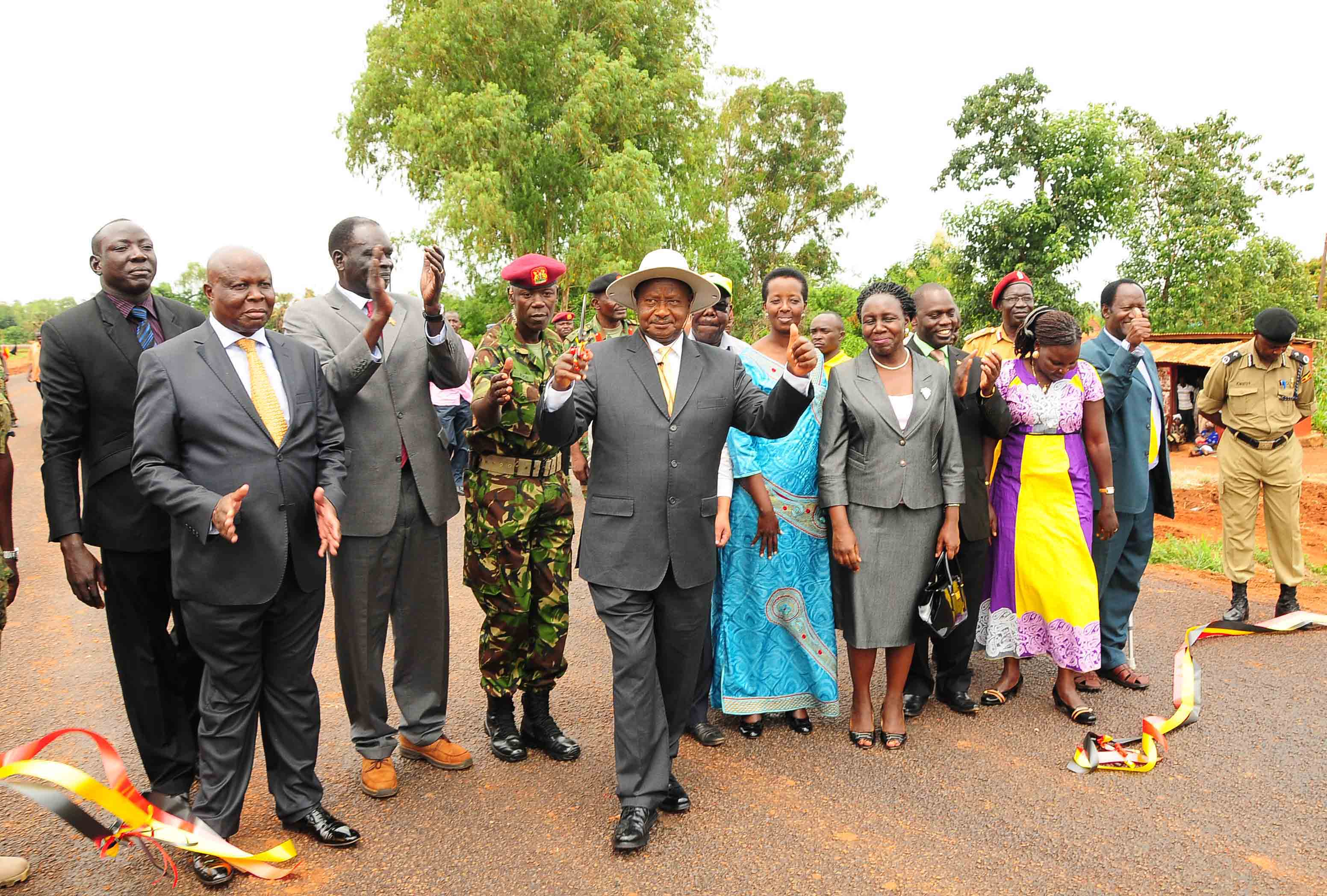 THUMBS UP: President Yoweri Museveni showing his victory sign after  commissioning Gulu- Atiak Road constructed by China HE NAN International Company yesterday. On his right is Project Manager Jin Pai Zhang, UNRA ED Allen Kagina. PHOTO BY ENOCK KAKANDE
