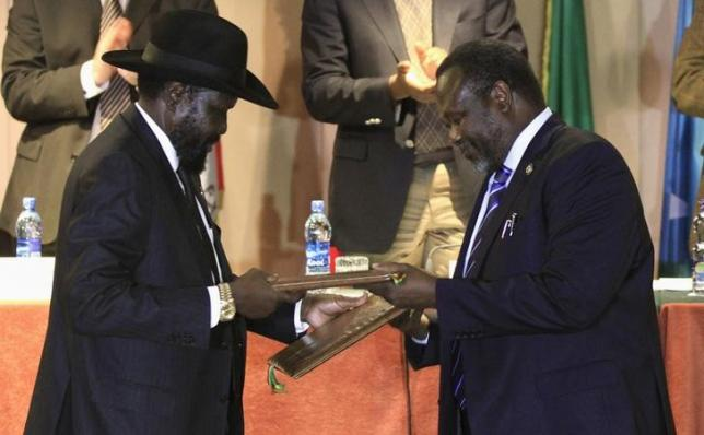 South Sudan's President Salva Kiir (L) and South Sudan's rebel commander Riek Machar exchange documents after signing a ceasefire agreement during the Inter Governmental Authority on Development (IGAD) Summit on the case of South Sudan in Ethiopia's capital Addis Ababa, Feburary 1, 2015.