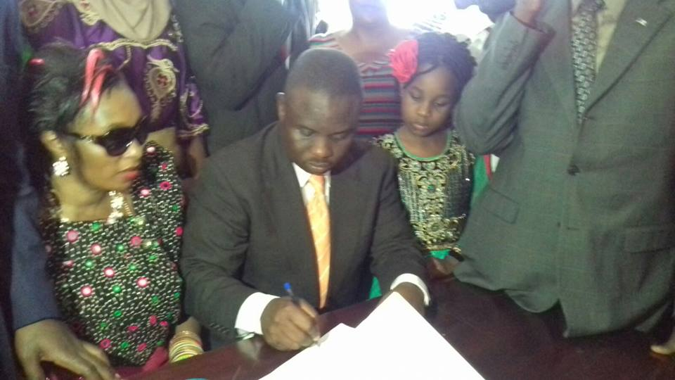 Flanked by his daughter and wife, Erias Lukwago puts pen to paper on the nomination documents. ‬ Photo: Stephen Mcleish Kafeero